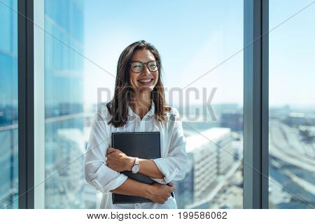 Happy business investor standing in her office in a highrise building overlooking the cityscape. Businesswoman in eyeglasses holding a document folder standing near window in office.