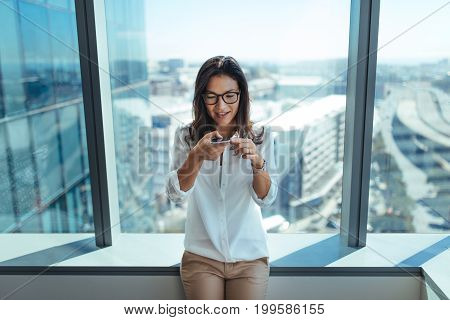 Young businesswoman sitting by the window of her office using mobile phone. Woman wearing eyeglasses using mobile phone for business communication.