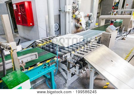 Conveyor with white briquettes chemical industry in Voronezh Sibur factory