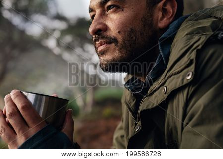 Close up shot of young caucasian man holding coffee taking break during hiking. Male hiker taking rest outdoors.