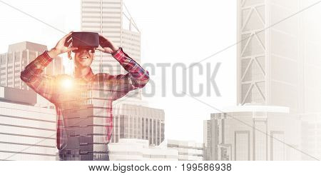 Young man with virtual reality headset or 3d glasses over cityscape background