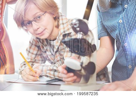 Look at me. Delighted pupil holding pencil in right hand leaning elbows on the table while looking straight at camera