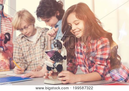 Interesting task. Pretty female classmate keeping smile on her face and looking into eyepiece while leaning on the table
