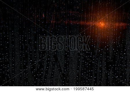 Water drops on glass with light and shadow at sunset.