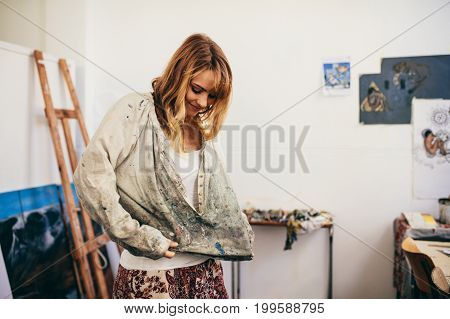 Young woman painter getting ready in her studio. Female artist wearing a shirt before starting work.