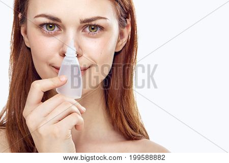Young beautiful woman on a light background holds drops for eyes, pharmacy, medicine.