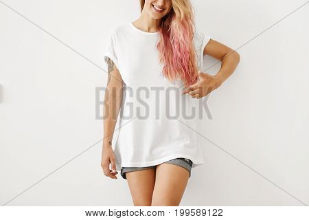 Cropped Shot Of Young Female In White Oversize T-shirt And Jean Shorts, Having Pink Hair Tips, Point