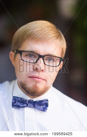 Young handsome man with short hair wearing a bow tie and posing in the city streets