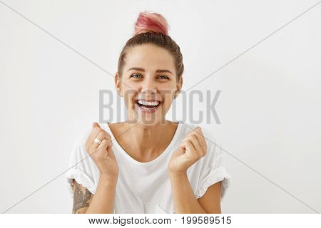 Attractive female with pinkish hair bun clenching her fists with joy being glad to recieve ticket abroad from her husband rejoicing her future holidays in exotic country together with her lover poster