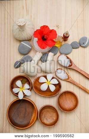 Spa treatment with salt in spoon ,ball ,towel, hibidcus on wooden board background