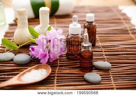 Spa setting with orchid, oil, soap on mat