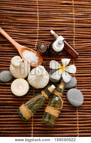 Spa treatment on mat with salt in spoon, oil ,stones, ball,