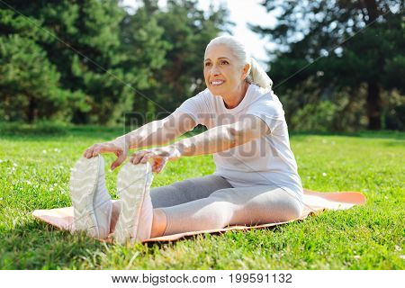 Stretch your back. Beautiful senior woman keeping smile on her face and sitting on the mat while looking forward