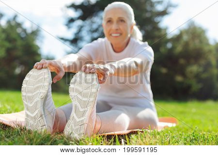 Touch your feet. Delighted smiling woman expressing positivity while stretching her back and enjoying fresh air