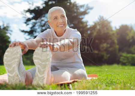 Look at me. Positive blonde female keeping smile on her face and putting hands on her trainers while looking aside