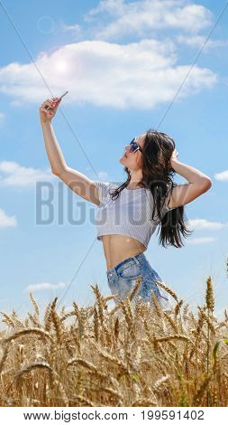 Girl in sunglasses doing self photo with her mobile phone on blue sky background.