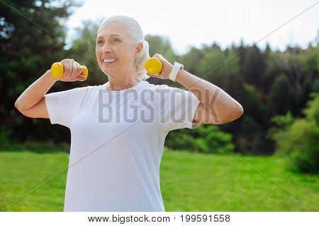 Keep fit. Positive delighted woman keeping smile on her face and holding arms bent in elbows while doing morning exercises