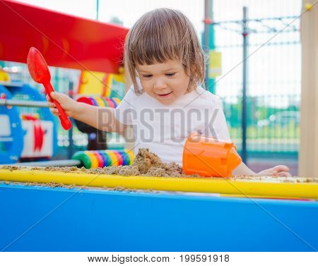 A girl in a sandbox holds a scoop and sculpts cakes