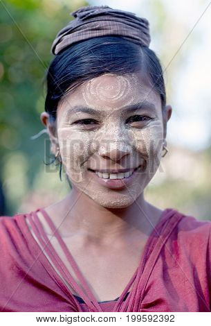 MYITKYINA, MYANMAR - JANUARY 4, 2012: Beautiful smiling Burmese girl with thanaka paste on her face posing for a photo at local market. Thanaka is a yellow cosmetic paste made from ground bark.