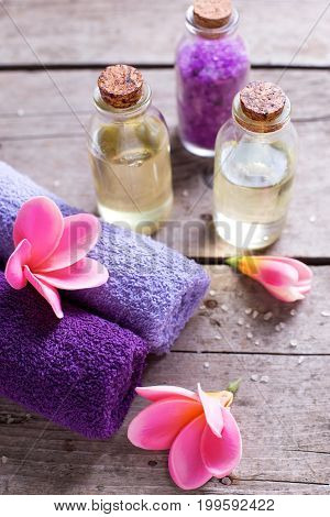Towels and bottles with oil on vintage wooden background. Selective focus is on towels.