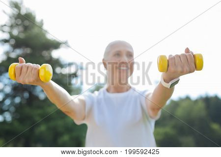 Bracelet for fitness. Attractive pensioner raising her arms while keeping dumbbells in both hands and looking sideways