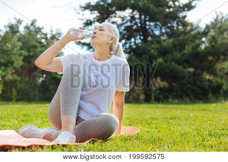 Have a break. Tired female person sitting on the mat and leaning on left arm while holding bottle of water in right one