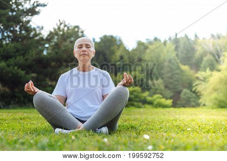 Time for meditation. Delighted mature woman crossing legs while sitting on the grass in yoga pose and enjoying silence around