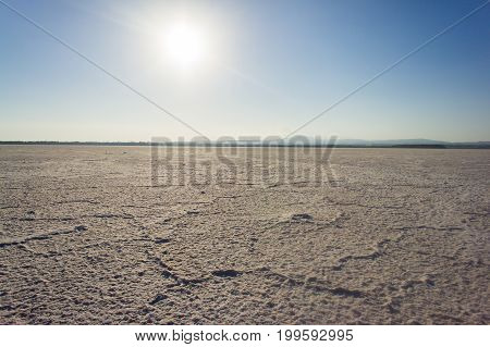 Backlit crusts of sea salt at Larnaca Salt Lake in Cyprus.