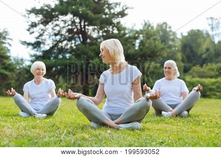 Follow us. Delighted mature sportswomen sitting on the grass and doing yoga while enjoying countryside