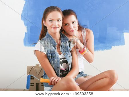 Two beautiful young woman doing wall painting, sitting on the floor