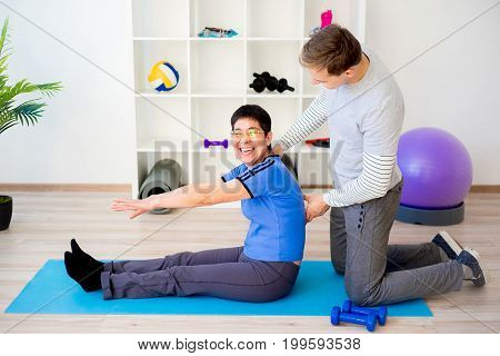 Physiotherapist helping a senior patient with exercise