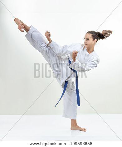 Girl athlete is training kick leg on the light background