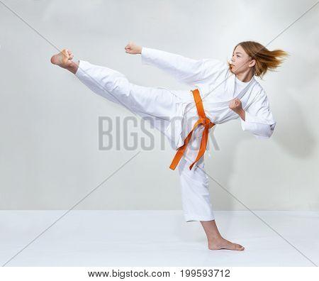 With an orange belt, an athlete trains a kick