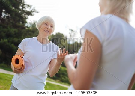 Lets do it together. Beautiful mature woman keeping smile on her face and holding sport equipment while being ready for training