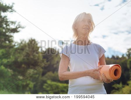 Looking for place. Attentive elderly woman holding her mat in left hand and looking forward while standing over beautiful background