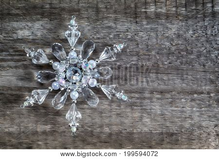 Christmas Gift snowflake made of glass on an old wooden surface space for text retro style