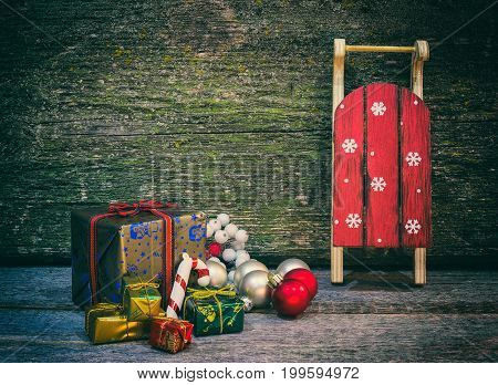 Christmas gift boxes and sleigh with presents on an old wooden surface space for text retro style