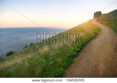 footpath in the mountains in the background rising above the sea of the sun