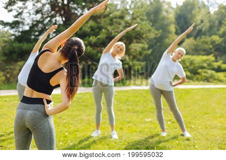 Repeat after me. Sporty girl wearing tank top and leggings, raising left arm while demonstrating exercise
