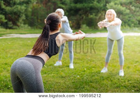 Follow my example. Sporty woman stretching her arms while bowing back and standing opposite her clients