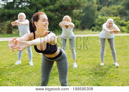 It is good for health. Attractive female person keeping smile on face and turning head while demonstrating exercise