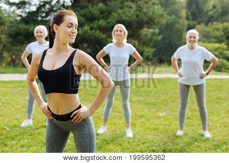 Slim body. Delighted woman expressing positivity and keeping back straight while looking aside