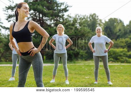 My group. Confident young fitness instructor keeping smile on her face and holding hands on the waist while controlling her visitors