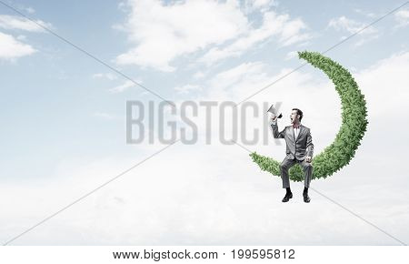 Young businessman sitting on green moon and screaming emotionally in megaphone