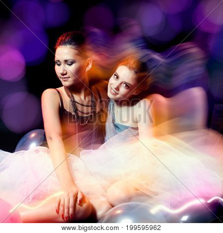 Two beautiful womans in tutu sitting on colorful background