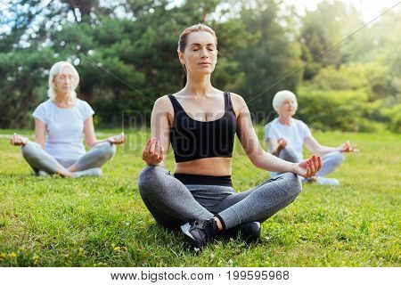 Follow your dreams. Serious woman keeping eyes closed and putting hands on knees while sitting on the grass