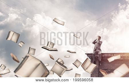 Young shocked businessman sitting on building top and covering eyes with palms