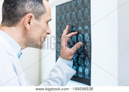 Carefully scrutinizing. The close up of a handsome middle-aged doctor analyzing the results of computer tomography, measuring the sizes with fingers
