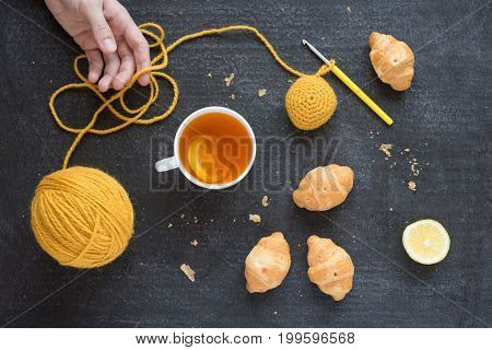Lemon tea, yellow crocheting and croissants on a plate. Female hand is also in the picture.