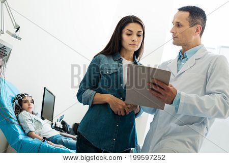 Bureaucratic details. Pleasant young doctor asking the mother of a little girl to fill out the form and put her signature while the girl undergoing electroencephalography